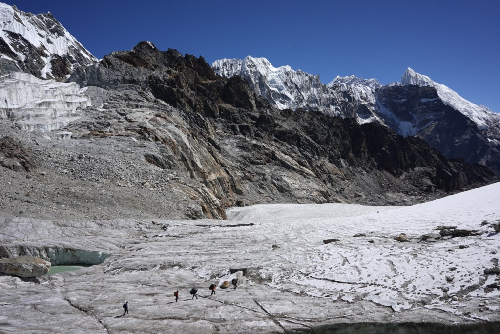 Porters cross the glacier below Cho La pass. Louche East Peak is visible in the back (far right). Photo: Zeb Blais.