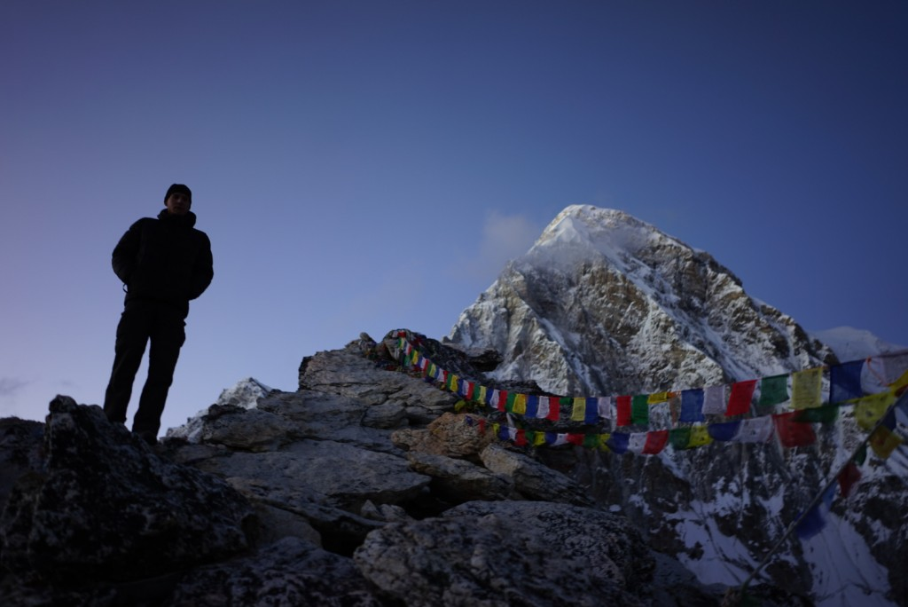 Prayer flags streaming from the top of Kala Patthar. Pumo Ri in the background. Photo: Zeb Blais.