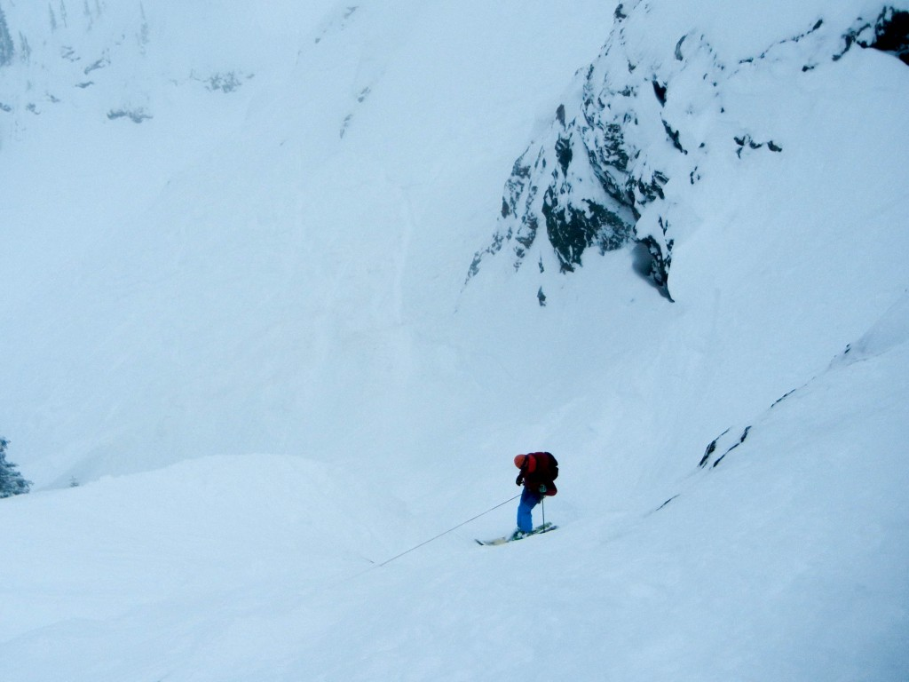 Rogers Pass. A ski client being lowered into a steep couloir.